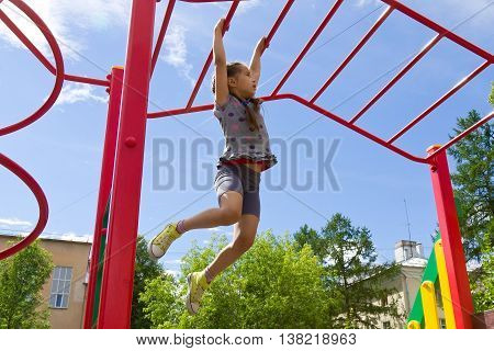 Little girl playing on a playground, hanging walk along the monkey bars