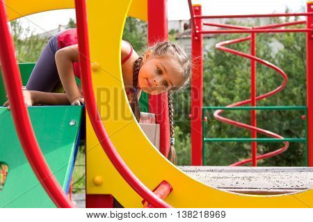 Portrait of cute, sportive little girl playing on the playground