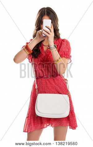 Lady in dress holds phone. Bracelets and watch on hands. Stylish girl wearing red dress. Phone call home.