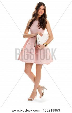 Girl in short salmon dress. Young woman is smiling modestly. Summer outfit with white purse. Evening outfit idea.