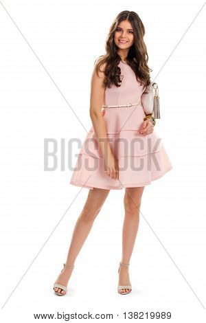 Lady in salmon evening dress. Young woman is smiling happily. Model wears attractive clothes. Designer dress and new bag.