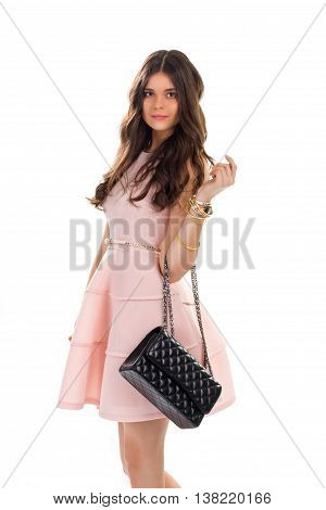 Girl wears light salmon dress. Black bag and short dress. Quilted leather purse with strap. Elegant accessory for evening outfit.
