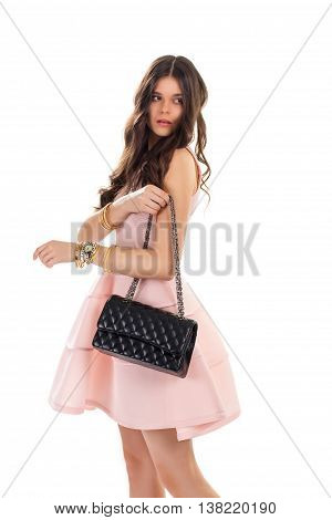 Woman with black bag. Short salmon dress and accessories. New handbag with chain strap. Trendy evening dress and purse.