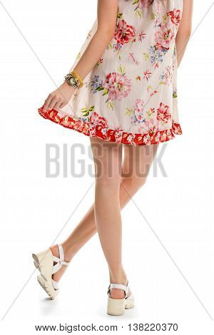 Woman in white floral dress. Watch and wedge shoes. Summer clothes from new collection. Light material and bright print.