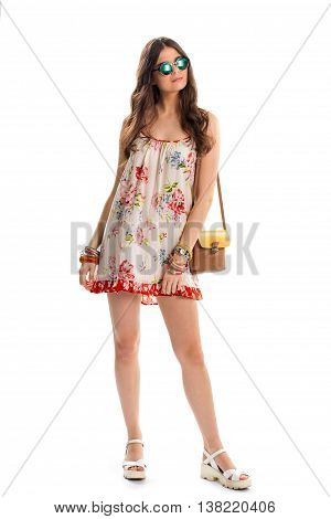 Girl in sleeveless floral dress. Wedge sandals and bicolor handbag. Stylish chameleon sunglasses. New summer trend.
