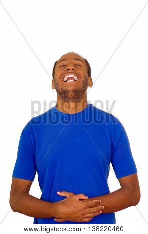 Man wearing strong blue t-shirt standing and laughing hard holding his stomach, white studio background.