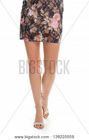 Lady's legs in beige heels. Floral dress with beige lining. Fashionable pink pattern. Elegant shoes from designer.