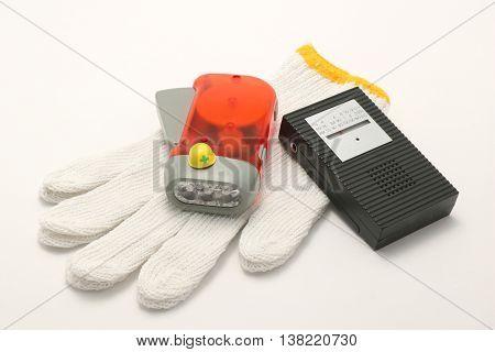 Helmet, portable radio, work gloves, and flashlight on white background. Emergency goods.