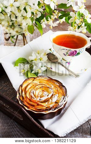 Apple rose shaped pie and cup of tea on the serving tray. Homemade apple cake for tea time. Breakfast tea with sweet apple pastry.