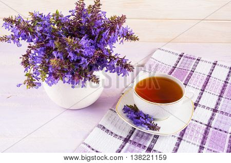 Cup of tea on checkered napkin and purple flowers. Summer tea time concept. Breakfast tea cup served with flowers.