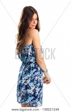 Woman in strapless floral dress. Girl looks back over shoulder. Light cotton garment for summer. Charming fashion model.