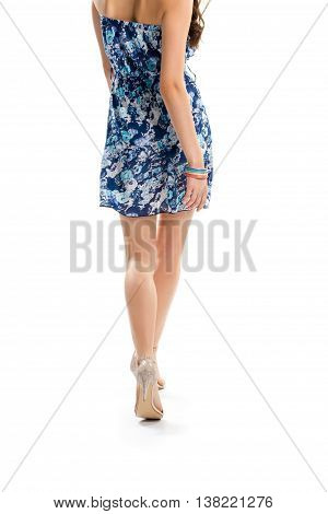 Lady in floral dress walking. Heel shoes of beige color. Garment with fashionable print. Light and attractive clothes.
