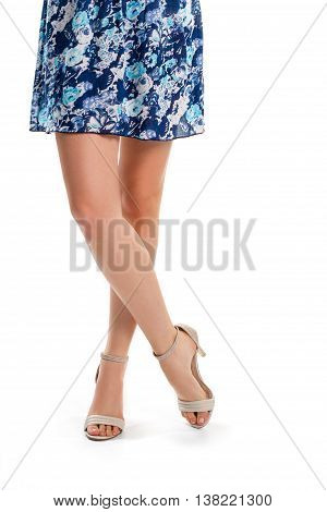 Lady's legs in heels. Beige shoes and short dress. Summer garment with flower pattern. Ease and comfort.