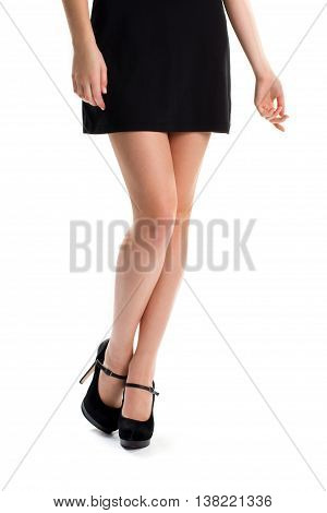 Girl's legs in black heels. Short dress and footwear. Luxury and expensive suede shoes. New collection of evening wear.