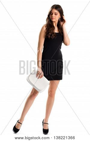 Lady in short black dress. White handbag and black footwear. Model wears expensive earrings. Beautiful evening outfit.