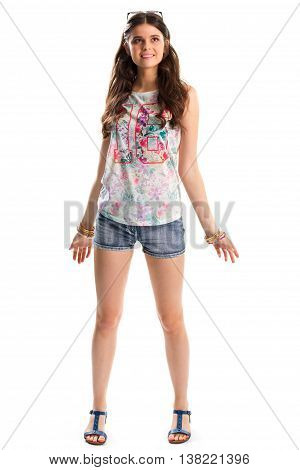 Woman in tank top smiling. Denim shorts and blue sandals. Stylish top with print. Summer outfit with colorful bracelets.