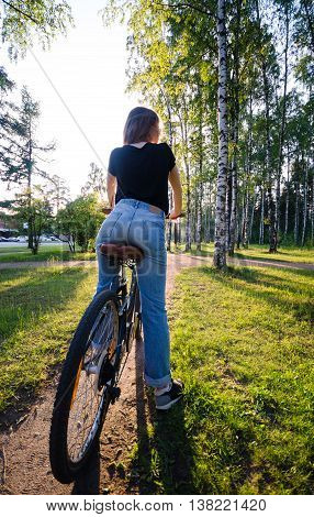 Woman ride by bycicle in park in the evening. View on girls back.