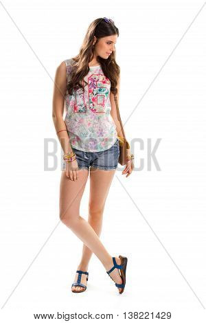 Girl in floral tank top. Short denim shorts and sandals. Pink print on summer garment. Trendy outfit with new accessories.
