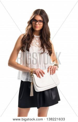 Woman in sleeveless blouse. Lady in glasses holds purse. Pretty girl on blank background. Leather skirt and expensive bracelets.