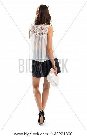 Young girl wears short skirt. White handbag and black heels. Nice evening outfit with accessories. Expensive bracelets of gold.