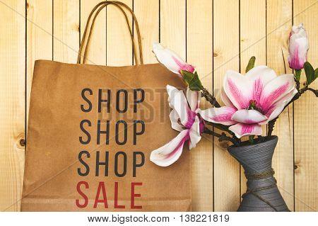 A paper shopping bag near a flower