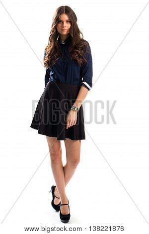 Woman in navy shirt. Black skirt and watch. Cotton clothing and suede heels. Smart casual outfit with accessory.