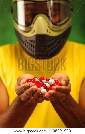 Closeup headshot man wearing yellow shirt, green and black protection facial mask holding up pile of paintball ammunition.