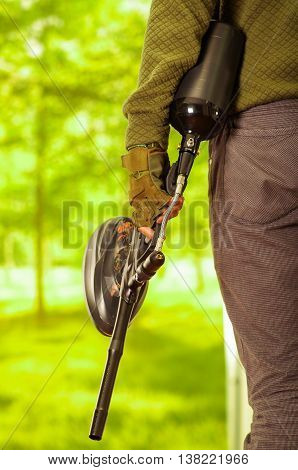 Closeup weapon with magazine held by man standing, forest background, paintball concept.