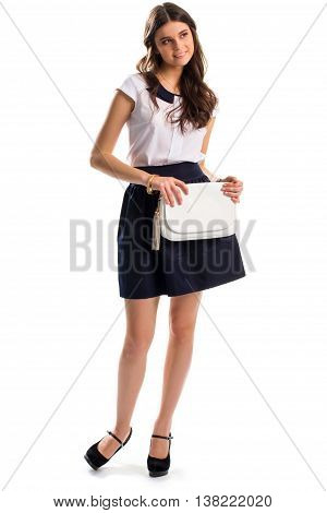 Smiling woman holds clutch bag. Navy skirt and black footwear. New apparel and accessories. Feminine spring outfit.