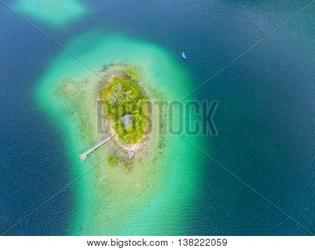 Aerial view to green island in blue sea. Natural background from tropical destination.