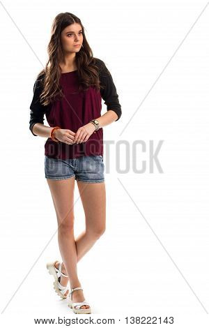 Lady in long sleeve top. Sandals and blue denim shorts. Red top with black sleeves. Model wears stylish summer outfit.