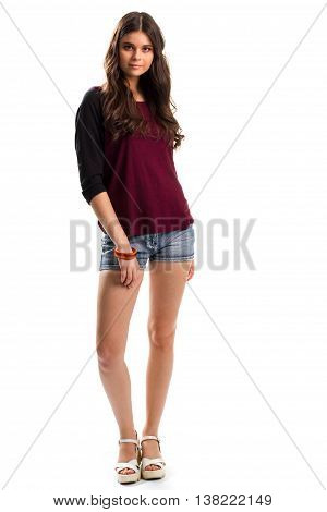 Woman in shorts and sandals. Dark top with long sleeves. Fashionable wedge shoes. Outfit from new collection.