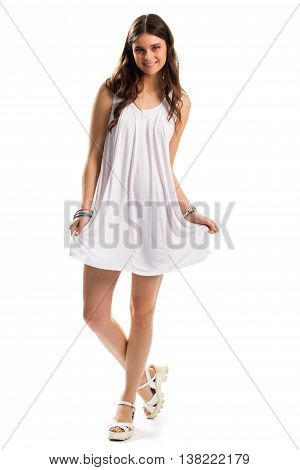 Woman in sarafan is smiling. White clothes and colorful bracelets. Comfortable everyday apparel. Model poses on camera.