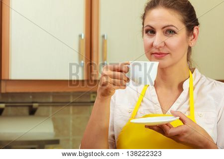 Mature woman in apron holding cup of coffee in kitchen. Housewife female with hot energizing beverage. Caffeine energy.