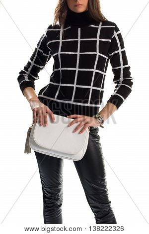 Woman holds white clutch bag. Black chekered pullover and pants. Brand new autumn apparel. Leather of best quality.