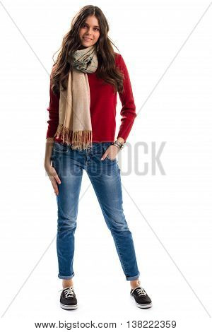 Woman wears pullover and scarf. Red sweater and denim pants. Autumn outfit with canvas shoes. New high-quality garments.