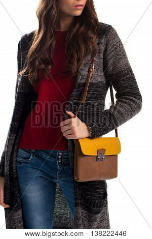 Lady in striped sweater coat. Blue jeans and bicolor bag. Brand new outerwear. Garment of wool and cotton.