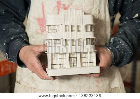Plaster Model Of Architectural Building Held By Person