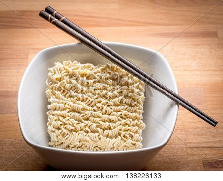 Ramen Instant Noodles Isolated in White Bowl on Wood Cutting Board