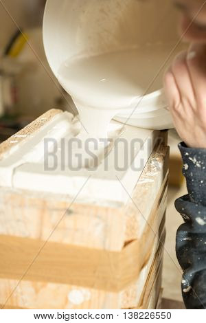 Liquid Plaster Being Poured Into Brimming Mold