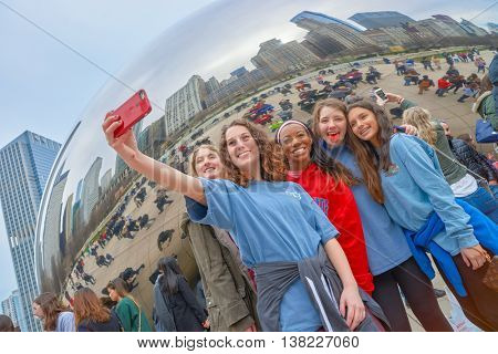 CHICAGO, IL - CIRCA MARCH, 2016: women taking a selfie near Cloud Gate. Cloud Gate is a public sculpture by Indian-born British artist Anish Kapoor.
