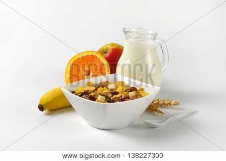 bowl of oat flakes, jug of milk and fruit on off-white background with shadows
