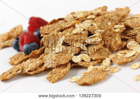 pile of breakfast cereal and berry fruits on white background - close up