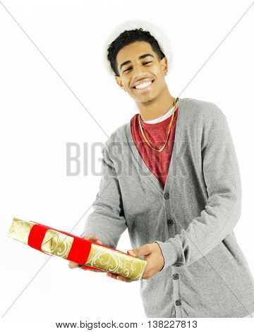 A tall teen man happily handing a wrapped Christmas gift to the viewer.  On a white background.