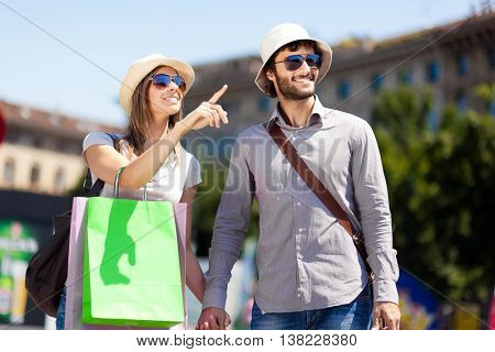 Happy couple of tourists shopping in the city
