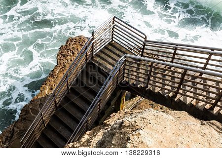 Bottom of beach access staircase at high tide, Ladera Street, Sunset Cliffs, San Diego, California.