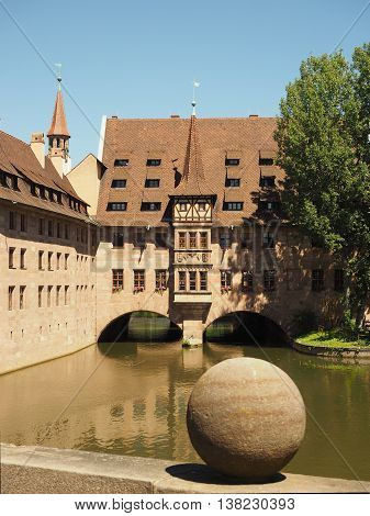 Nuremberg Germany - June 23 2016: Hospice of the Holy Spirit and old houses with the Pegnitz river