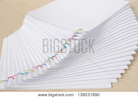 Colorful Paperclip With Pile Of Overload White Paperwork And Reports