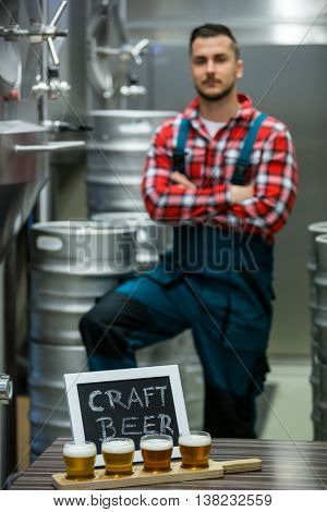 Four glasses of craft beer on beer sampler tray and brewer standing in background at brewery