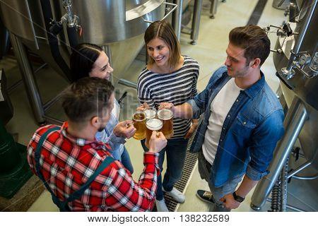 Happy brewers toasting beers at brewery